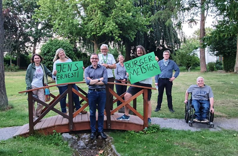 Sieben Kandidat*innen der Grefrather Grünen und der unabhängige Bürgermeisterkandidat Jens Ernesti stehen im Park hinter dem Oedter Rathaus